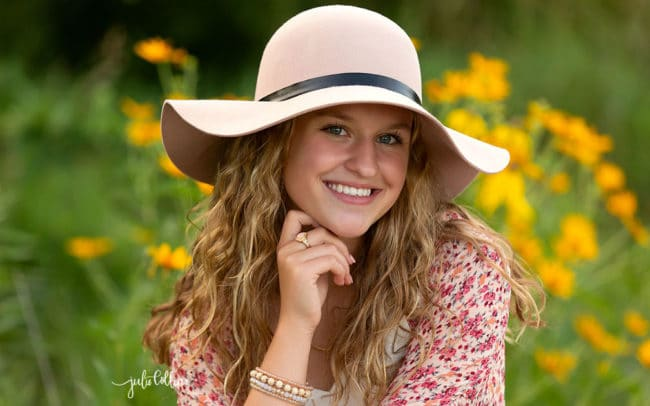 Senior girl in flower field with hat