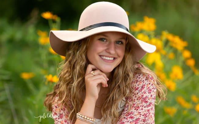 Senior girl in flower field with hat
