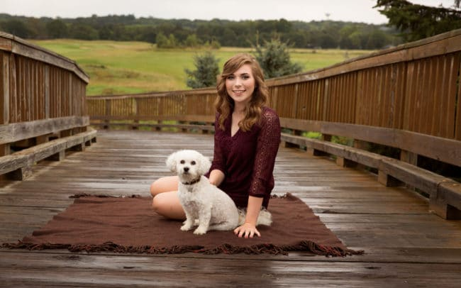 Photo of senior in high school sitting with dog on bridge