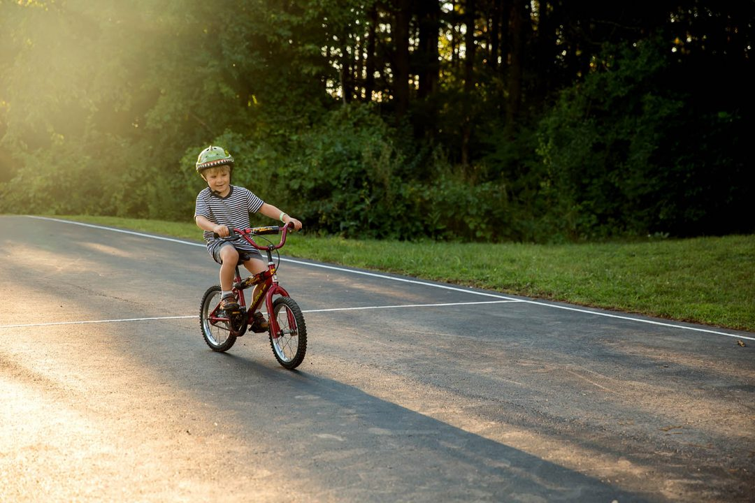 Four year old boy riding his bike in summer