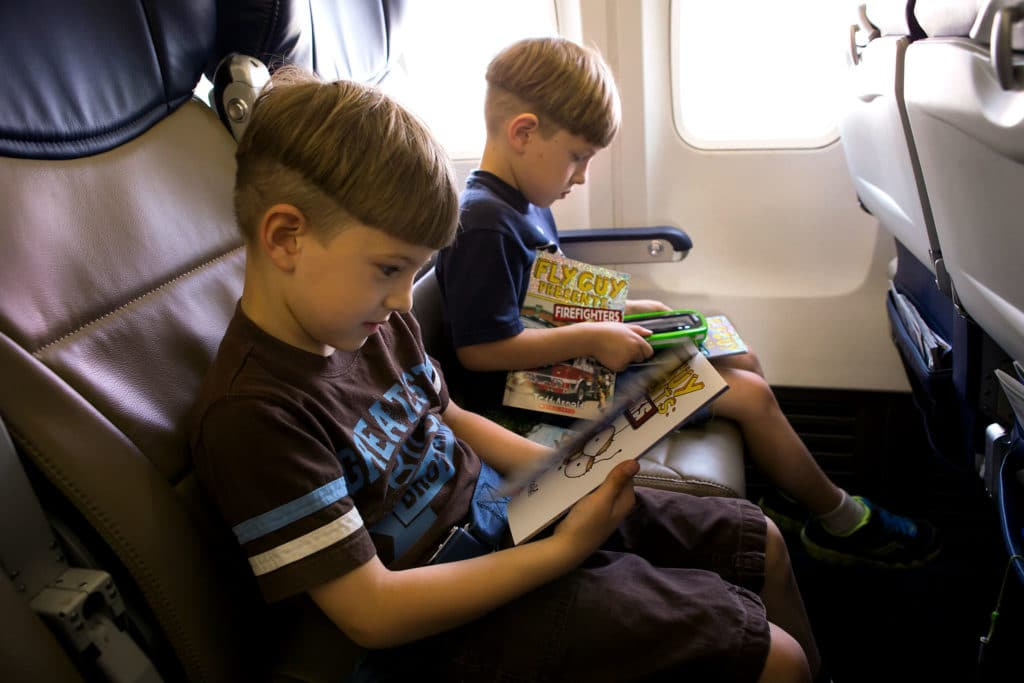 Boys reading books on a plane
