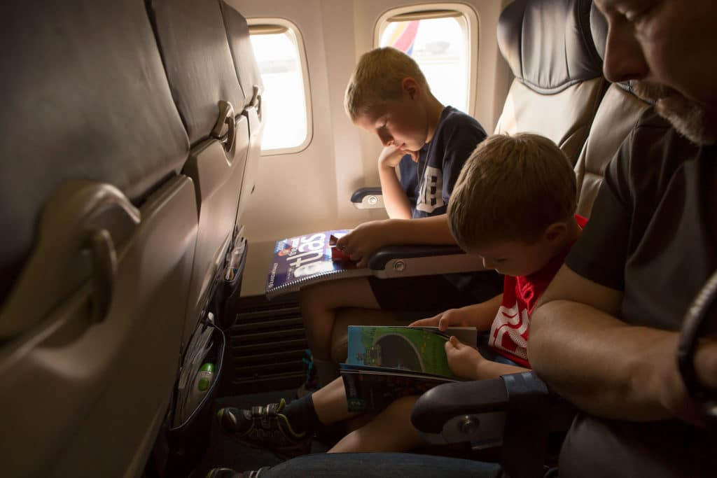 Boys looking at books on an airplane