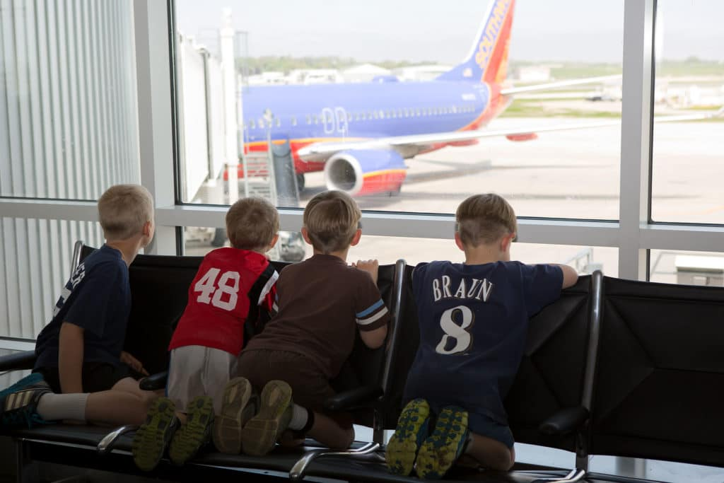 Four boys looking out airport window at a plane