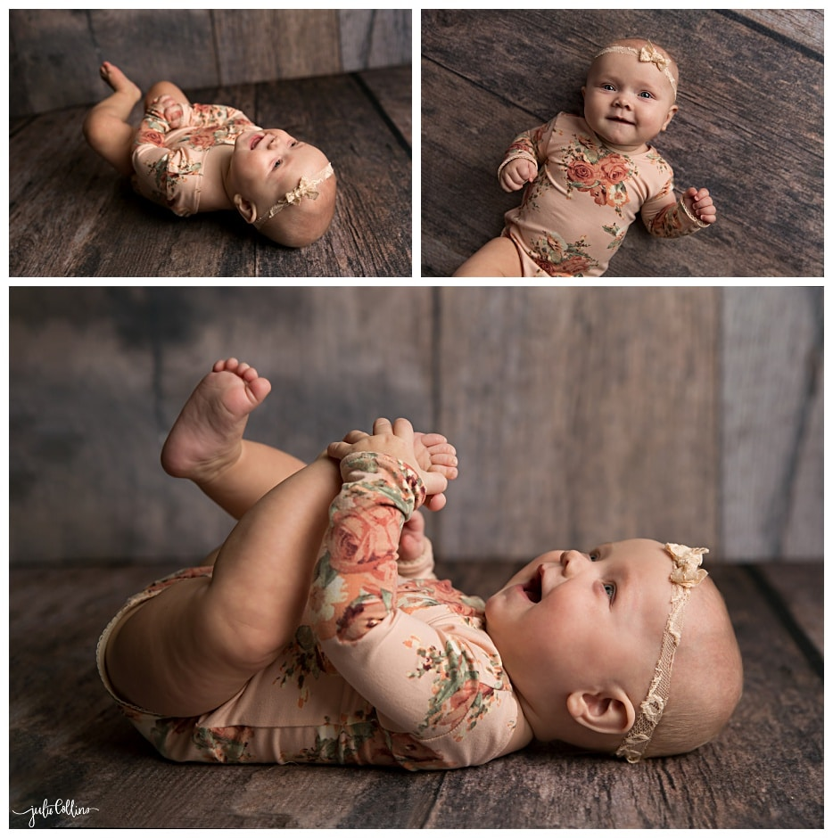 Baby girl laughing and smiling lying on wood floor
