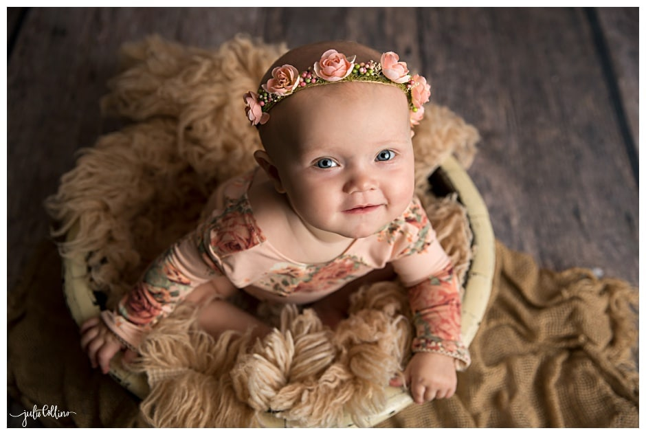 Baby girl sitting in bowl smiling