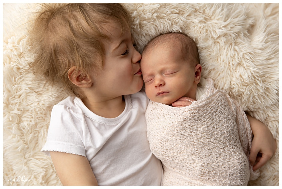 Big sister kissing baby sister on head