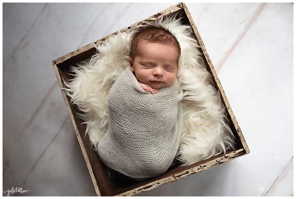 Newborn baby boy posed in a box prop