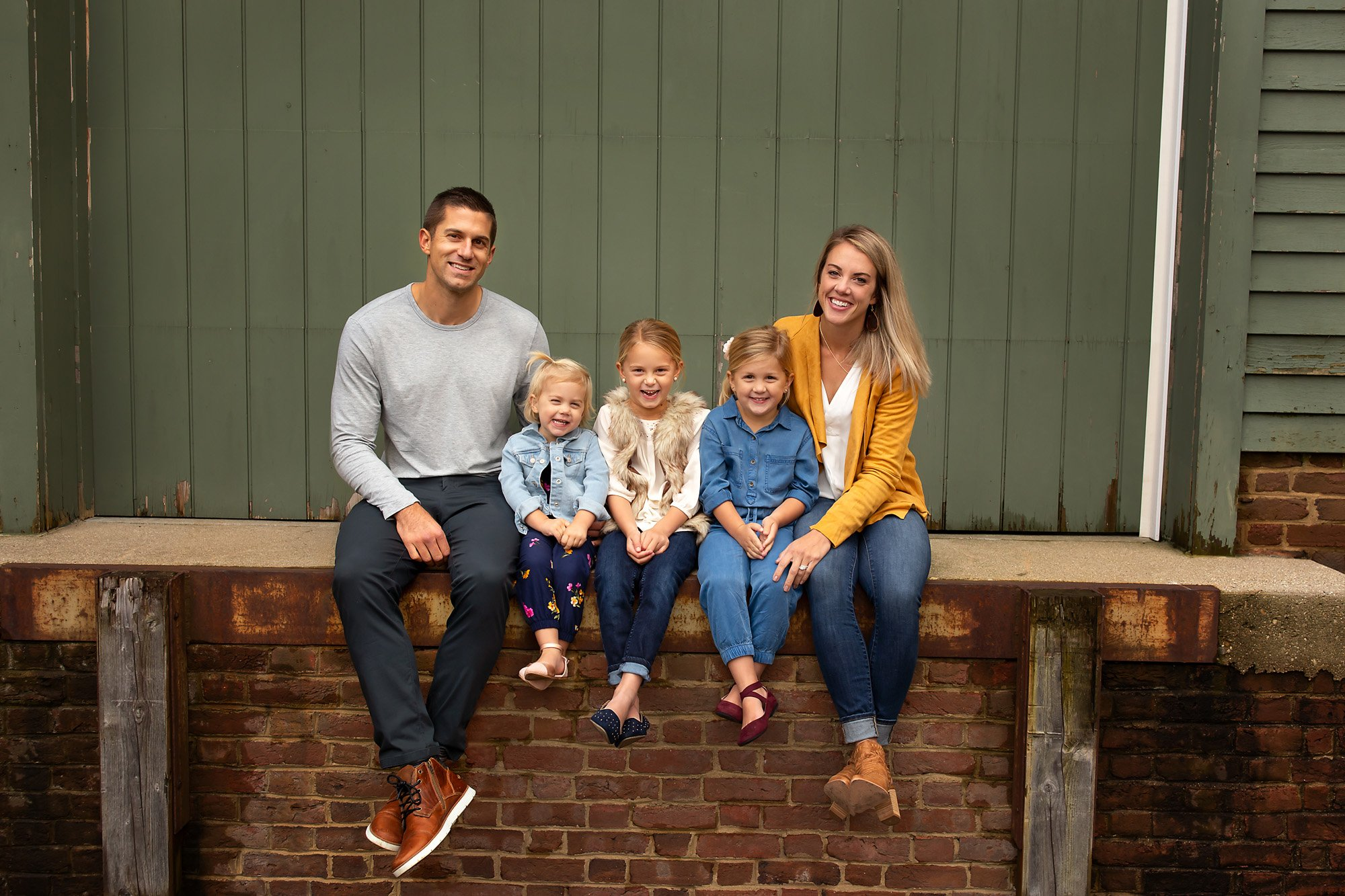 Family of 5 sits on a wall and poses during a family session with Julie Collins Photography