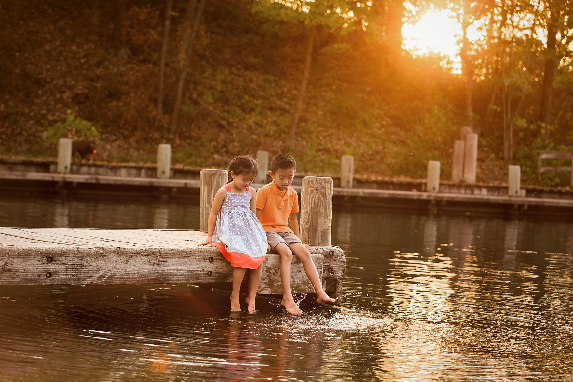 children sitting on a dock splashing their feet during a family session with Julie Collins Photography