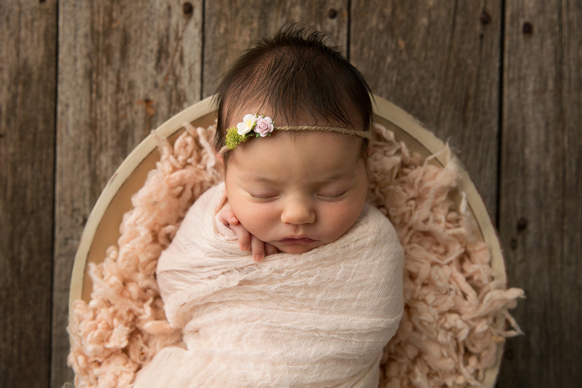 Photo of a Newborn wrapped in pink during a newborn portrait session with Julie Collins Photography