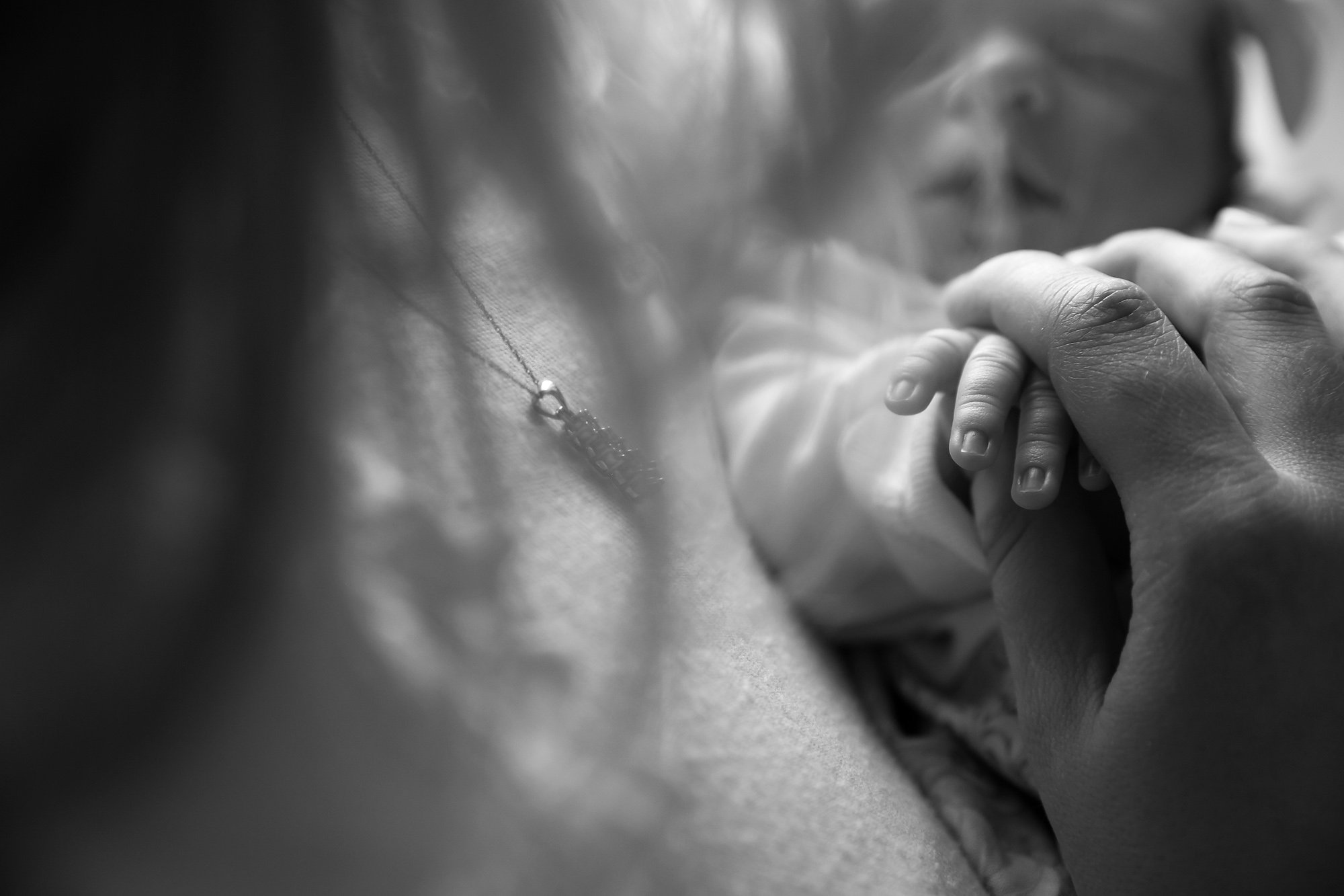 Black and White Newborn closeup of mother holding baby's fingers by Julie Collins Photography
