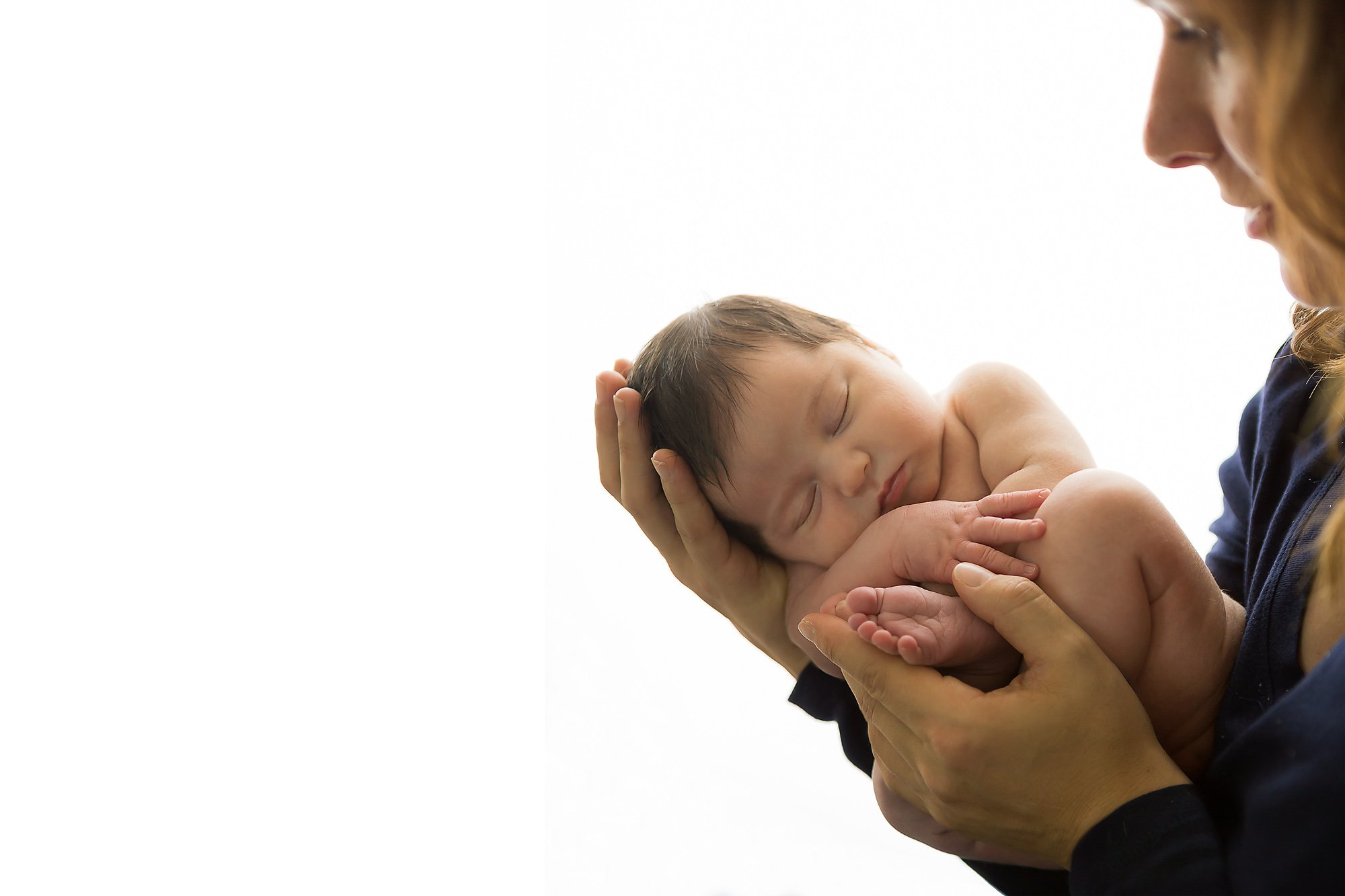 Newborn held in her mother's hands during an Oconomowoc Newborn Photography session