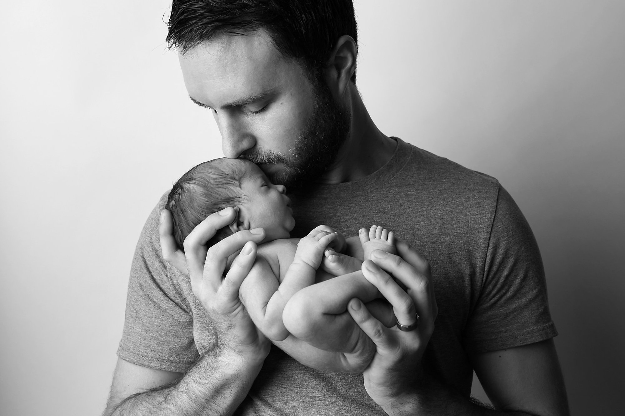 Father holding a newborn during a portrait session with Julie Collins Photography
