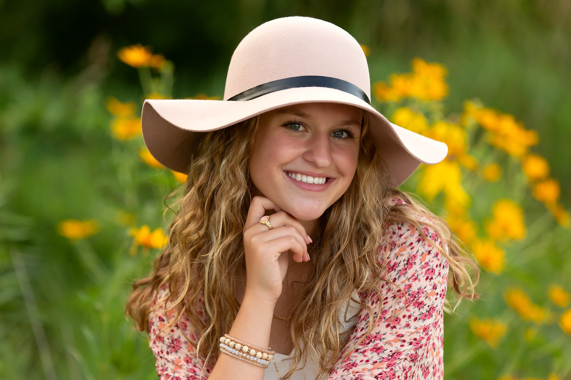 A high school senior girl poses with a hat in yellow flowers during a portrait session with Julie Collins Photography