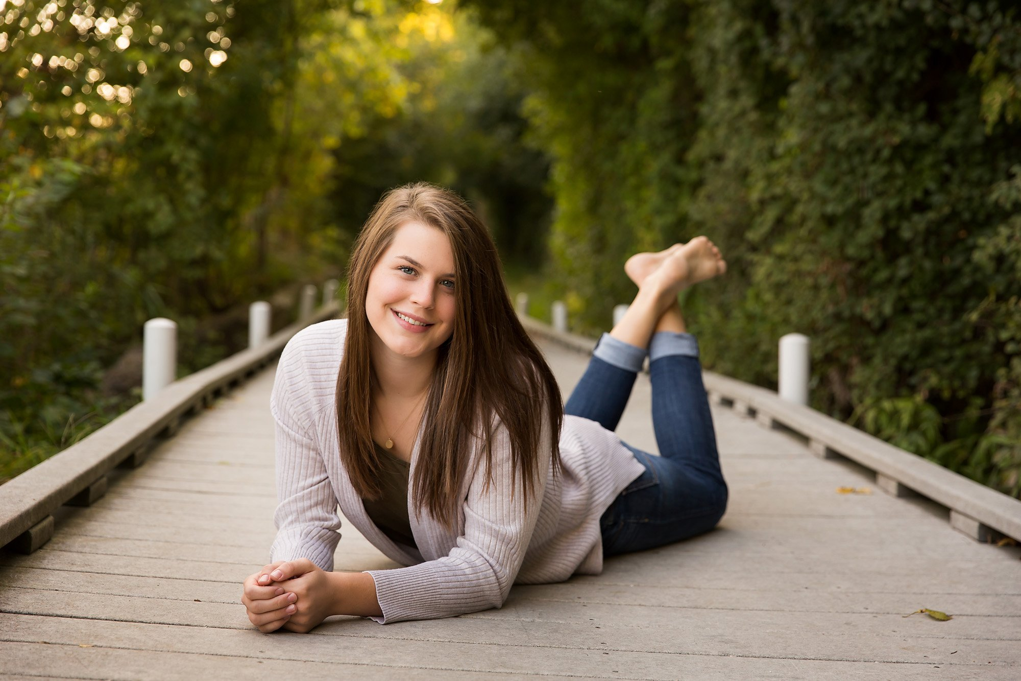 High school seniors girl laying on her stomach during a portrait session with Julie Collins Photography