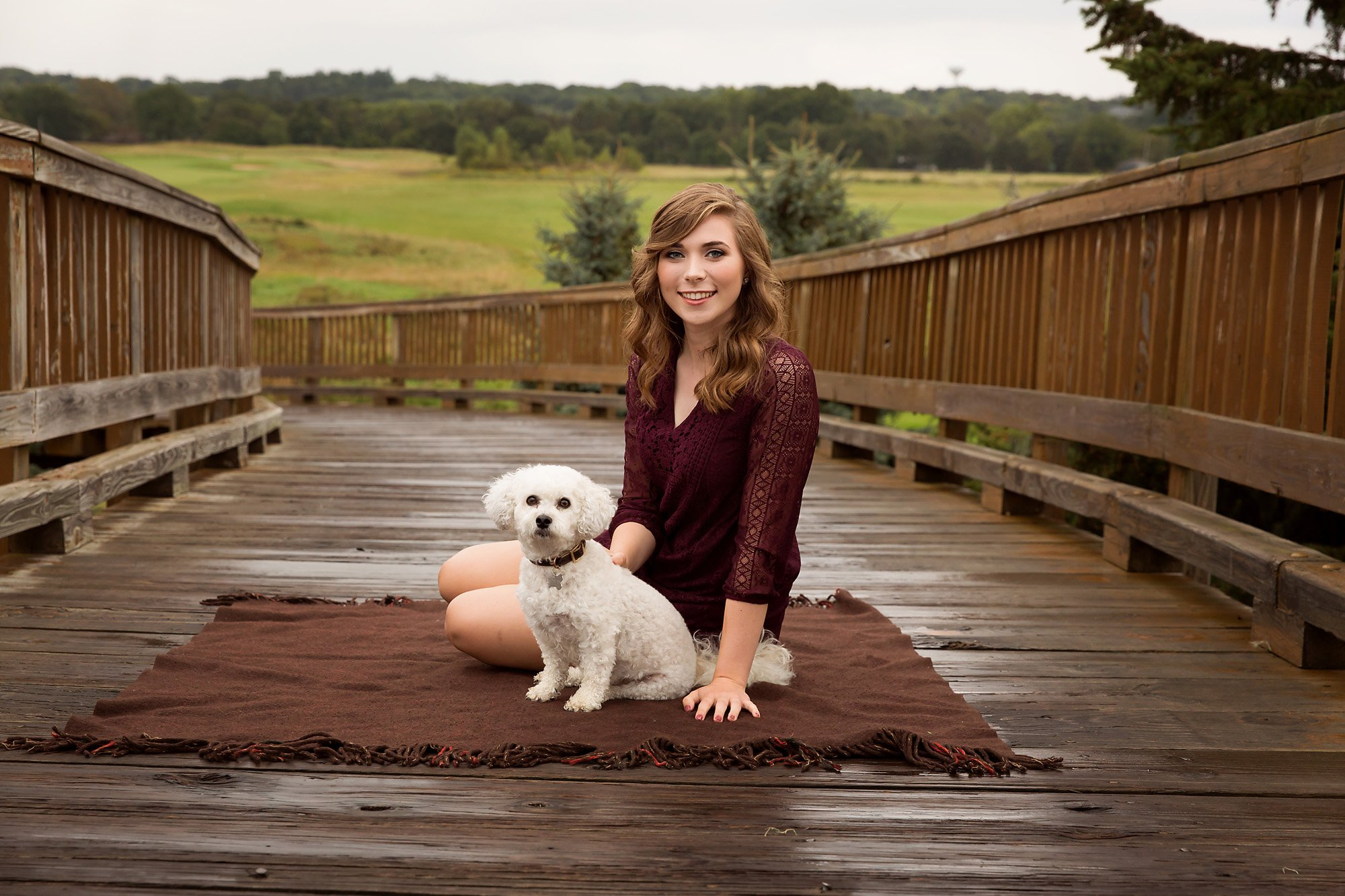 High school seniors girl posing with her dog during a portrait session with Julie Collins Photography