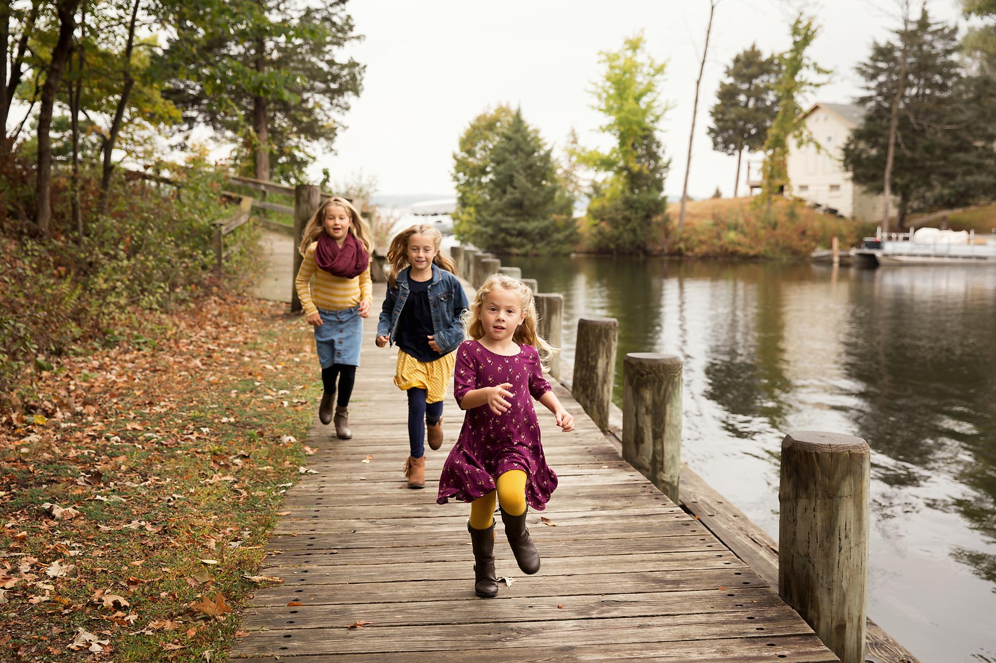 3 girls running on a dock during a family session with Julie Collins Photography