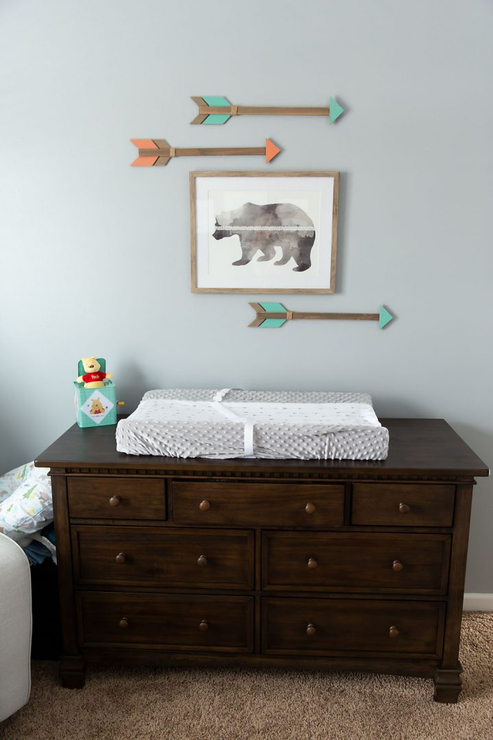 Nursery picture of dresser used as changing table, bear print with arrows on wall