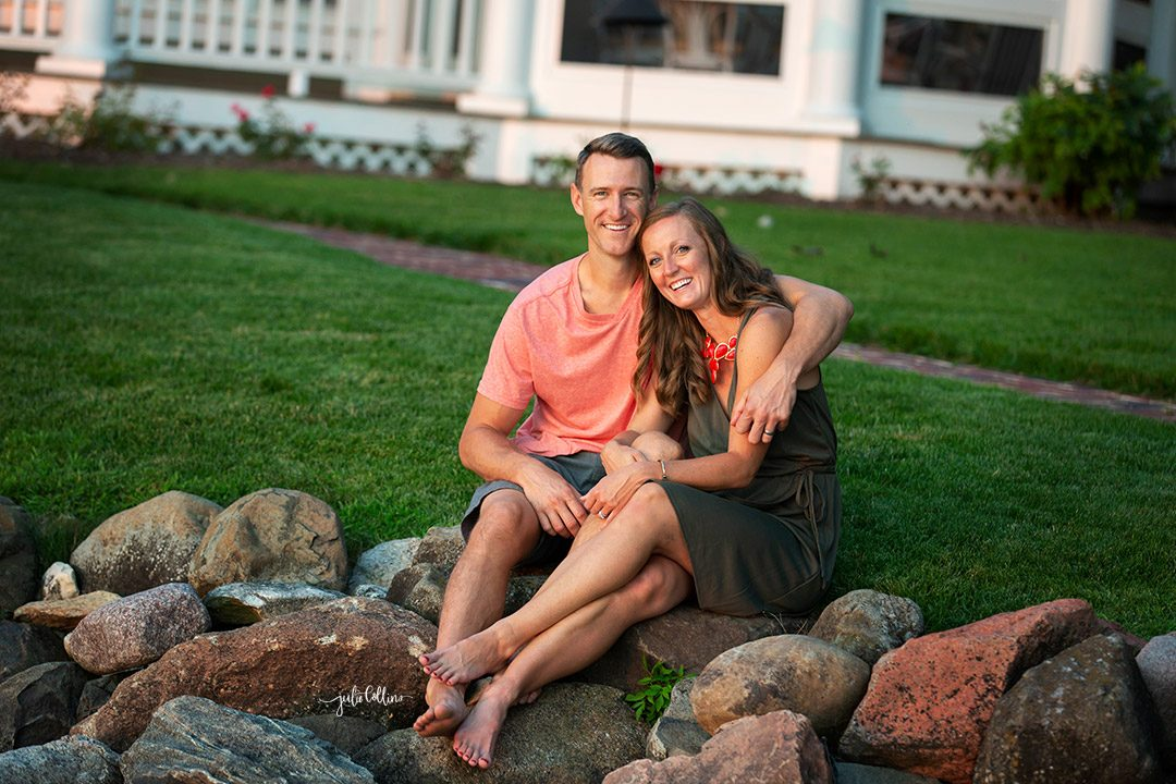 Couple laughing and posing for professional portrait outside of Oconomowoc family home on Lac la Belle