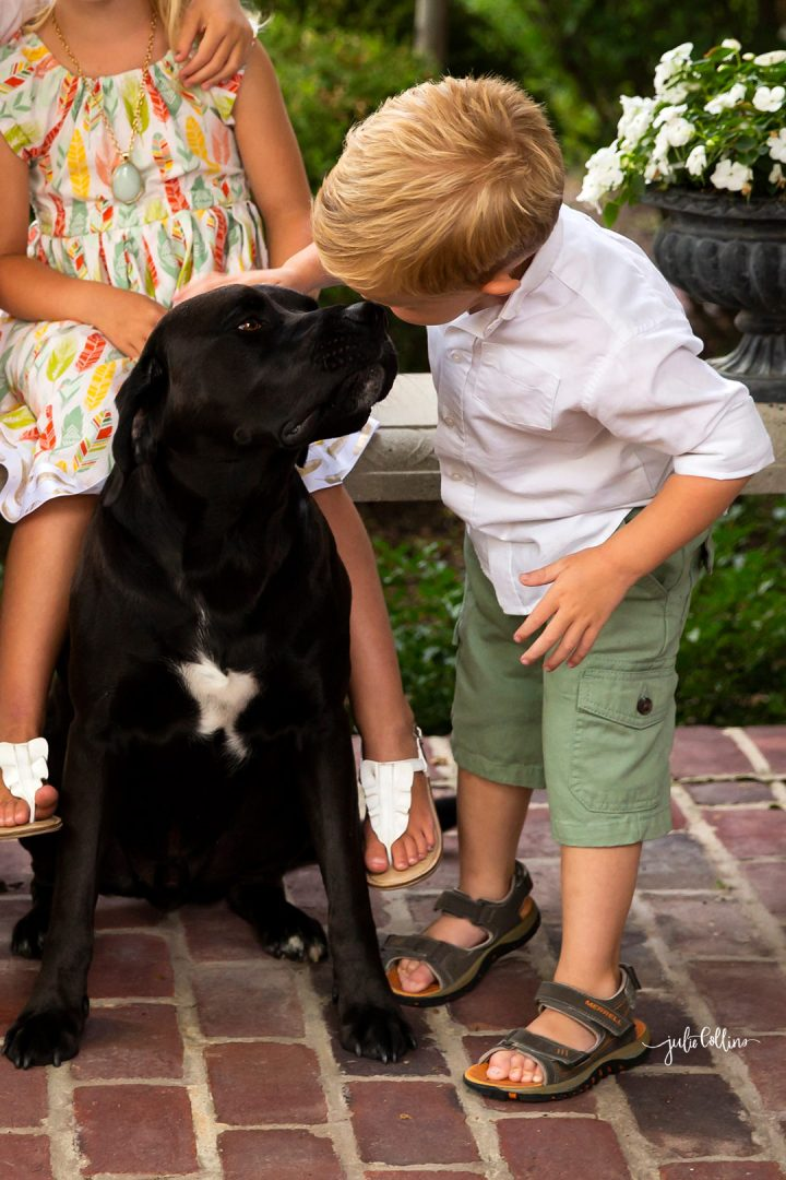 Three year old boy kissing his black labrador dog outside Oconomowoc family home on Lac la Belle