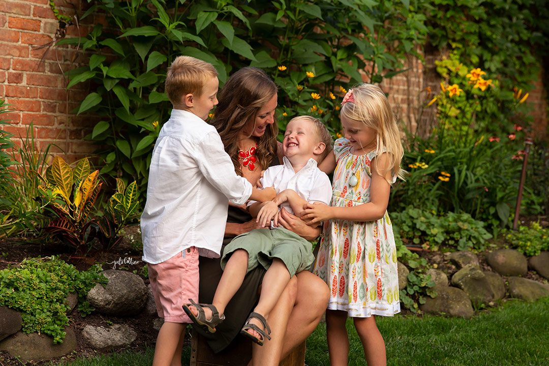 Mom with her three children in candid moment laughing together while tickling outside Oconomowoc family home on Lac la Belle