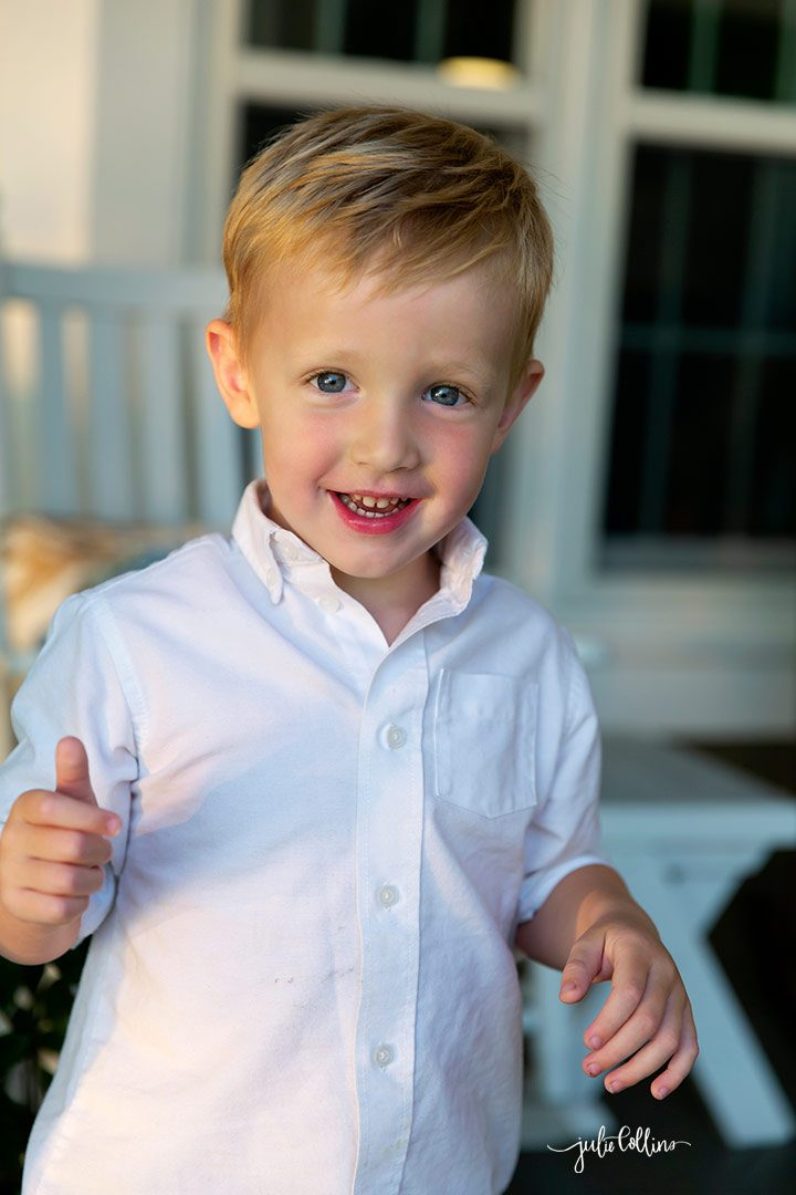 Three year old boy posing for professional portrait outside Oconomowoc family home on Lac la Belle
