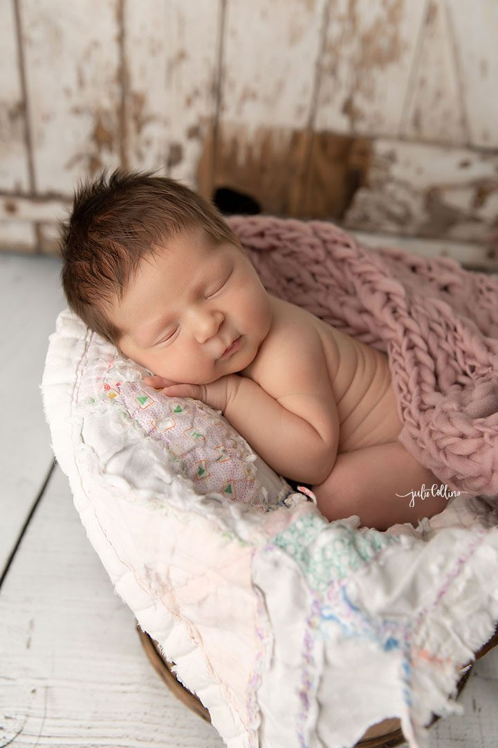 Oconomowoc newborn photographer captures baby girl sleeping in a basket surrounded in pink vintage layers with barnwood wall behind