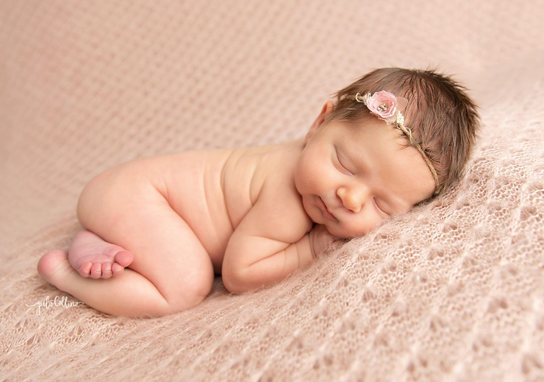 Oconomowoc newborn photographer captures baby girl sleeping on pink blanket smiling