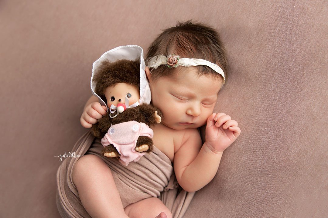 Oconomowoc newborn photographer captures baby girl sleeping in on a pink blanket holding a monchi chi baby doll