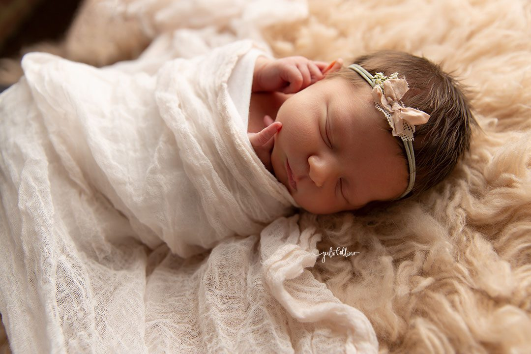 Oconomowoc newborn photographer captures baby girl sleeping in on a blush-colored fuzzy blanket, covered in pretty pink blanket