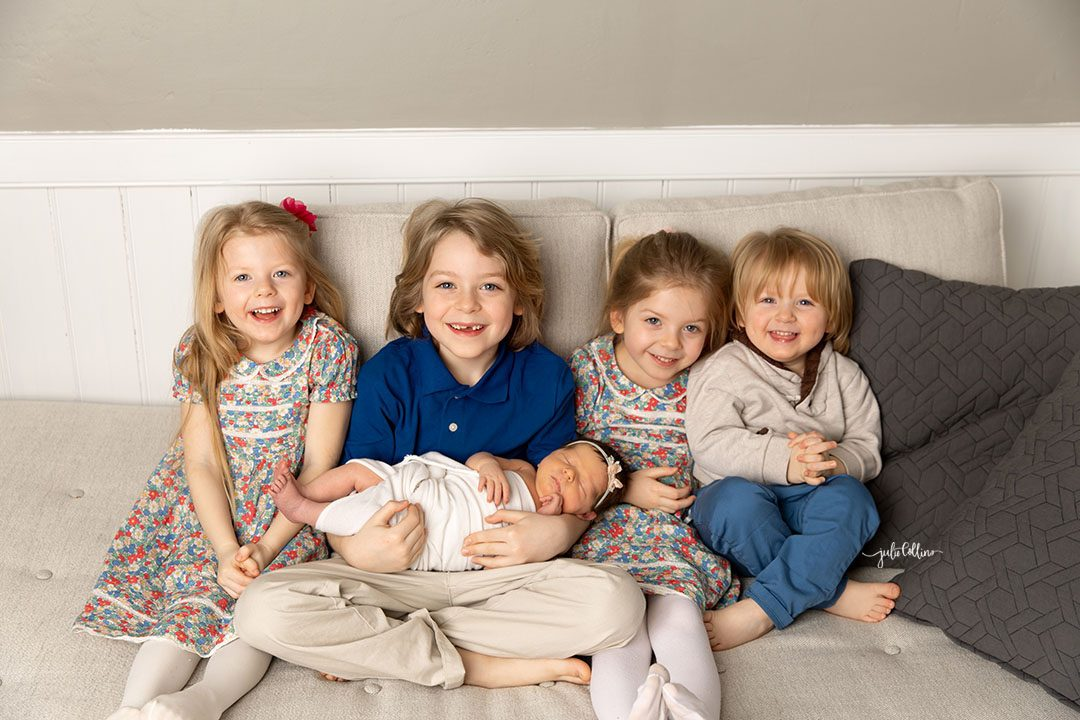 Oconomowoc newborn photographer captures baby girl sleeping in brother's arms with three other siblings on couch