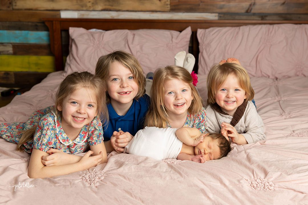 Oconomowoc newborn photographer captures newborn baby girl on bed with four siblings smiling at camera