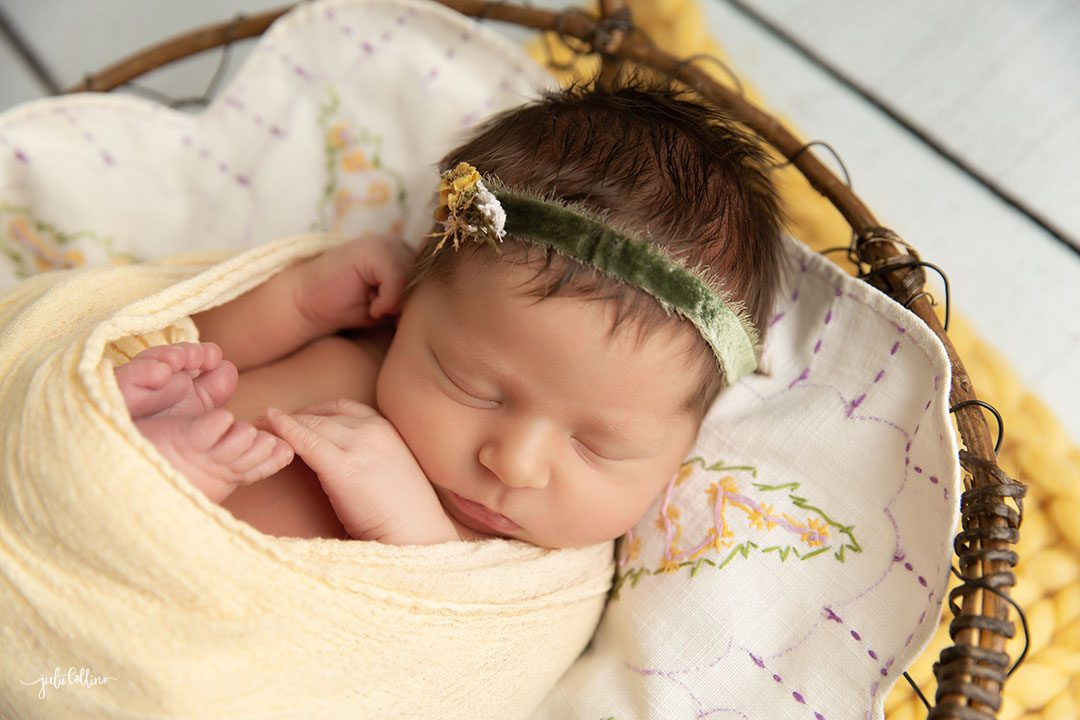 Oconomowoc newborn photographer captures baby girl sleeping in a basket surrounded by yellow vintage layers and accents