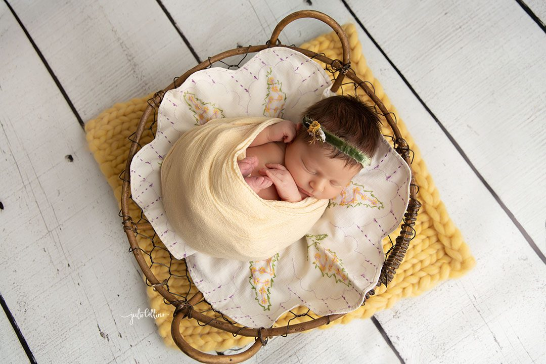 Oconomowoc newborn photographer captures baby girl sleeping in a basket with yellow vintage accents and details