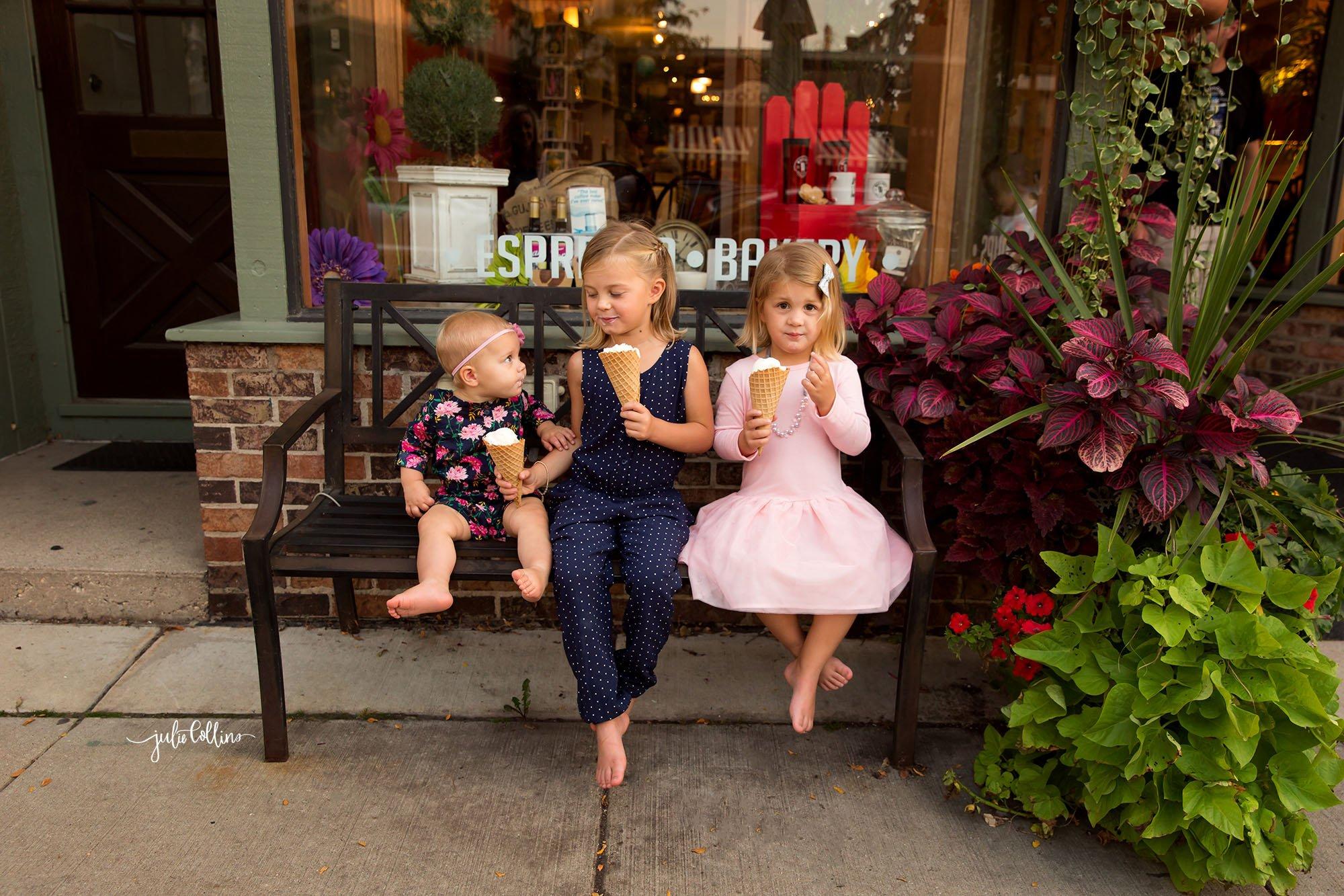 Three girls sitting on bench outside Oconomowoc ice cream shop eating ice cream