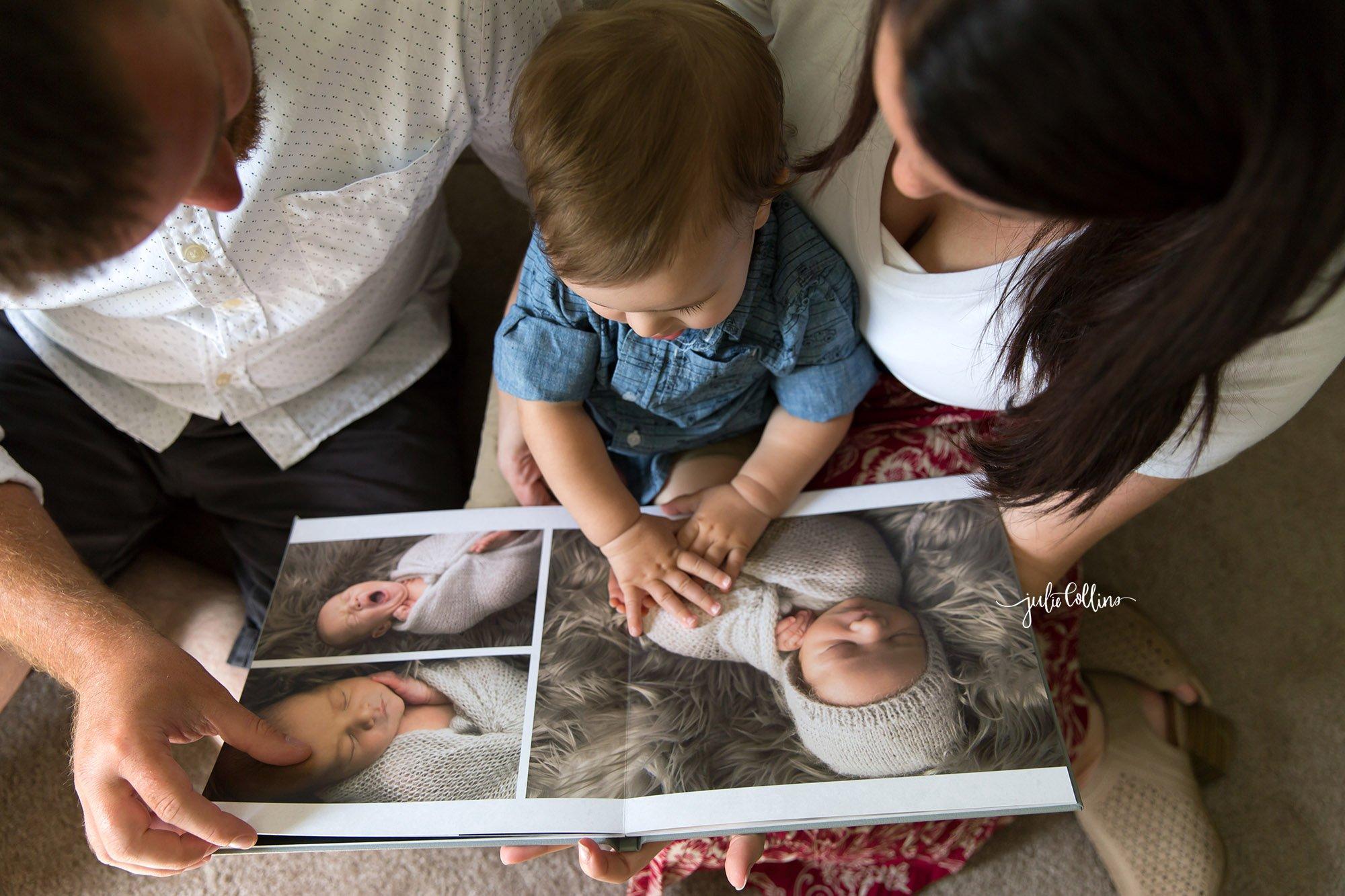 Family of three looking through baby photo album