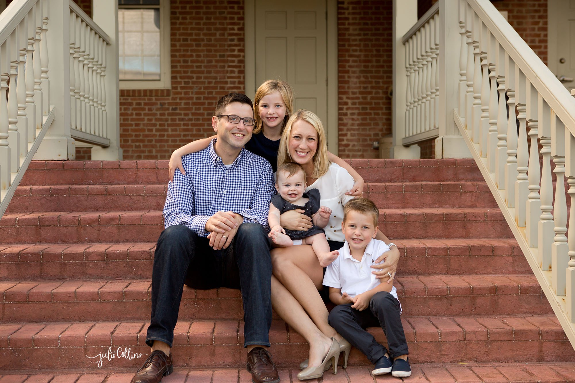 Family of five sitting on brick steps of urban area in downtown Delafield posing for a family portrait session