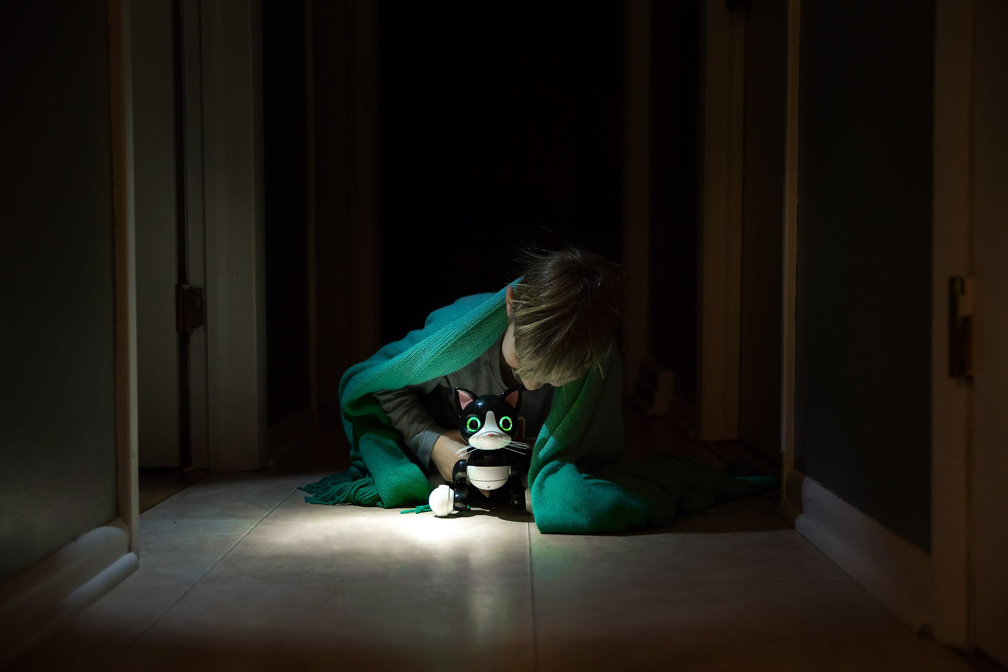 five year old boy with his green eyed electronic cat toy in a dark hallway