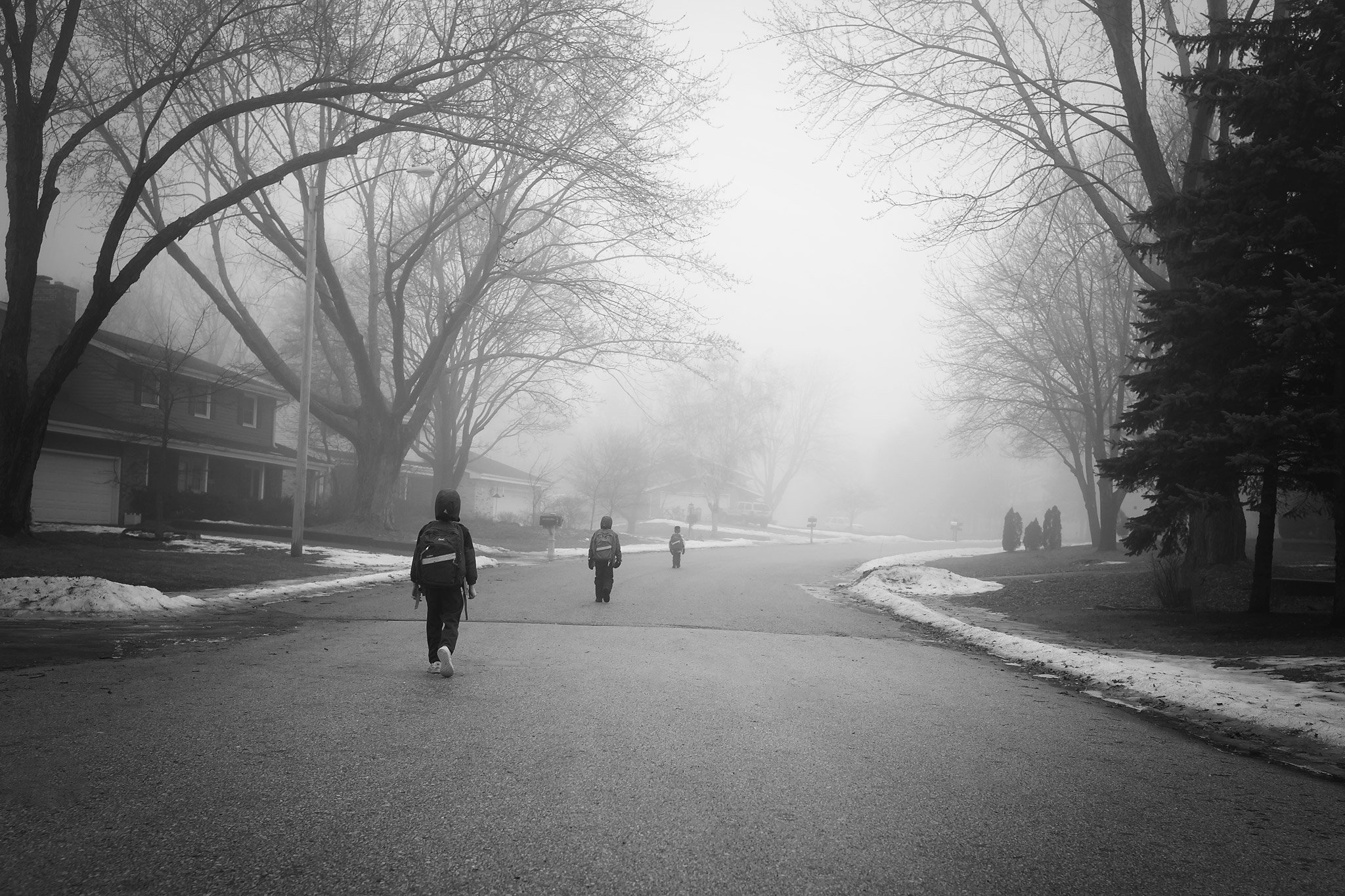 Three kids walking to the bus stop in foggy weather