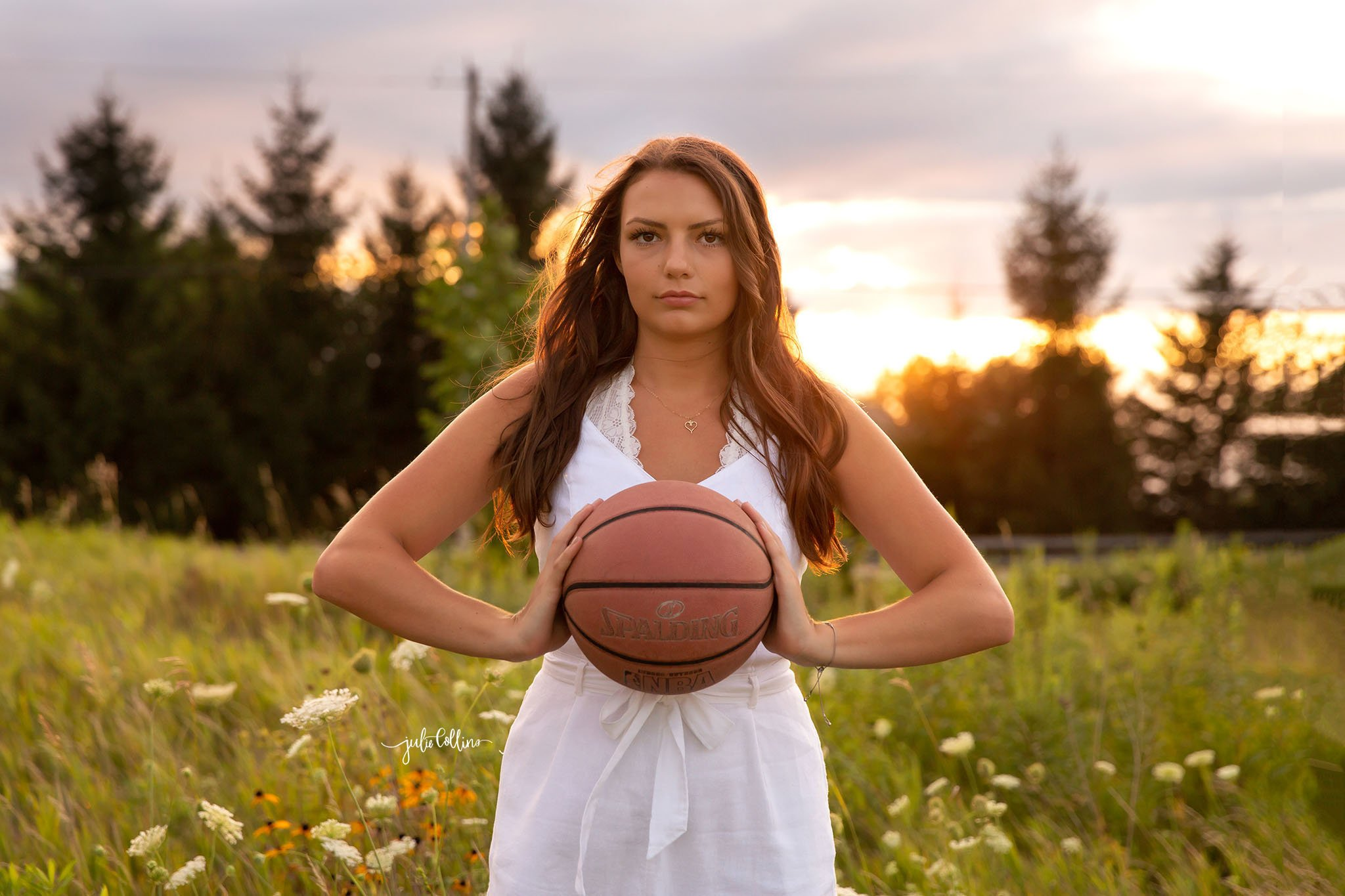 High school senior in white jumper looking at camera with basketball in field in Delafield, Wisconsin