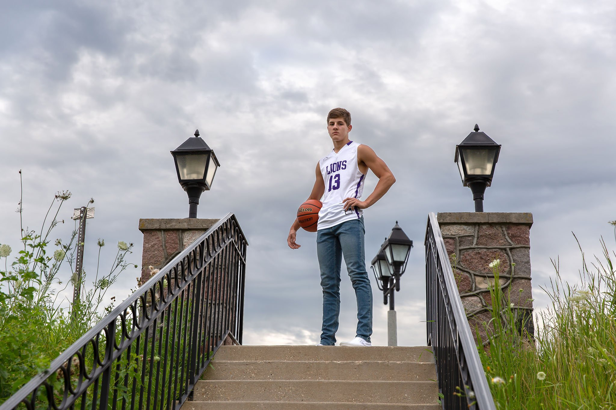 High School Senior boy in basketball uniform looking at camera in Delafield, Wisconsin at Cushing Park