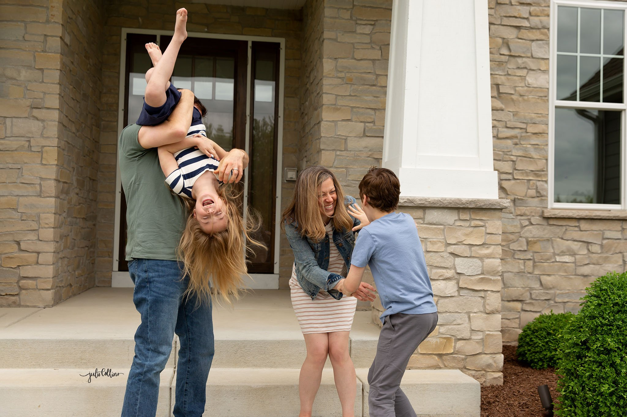 Family of four in tickle fight on their Pewaukee front porch during a Pewaukee photo session