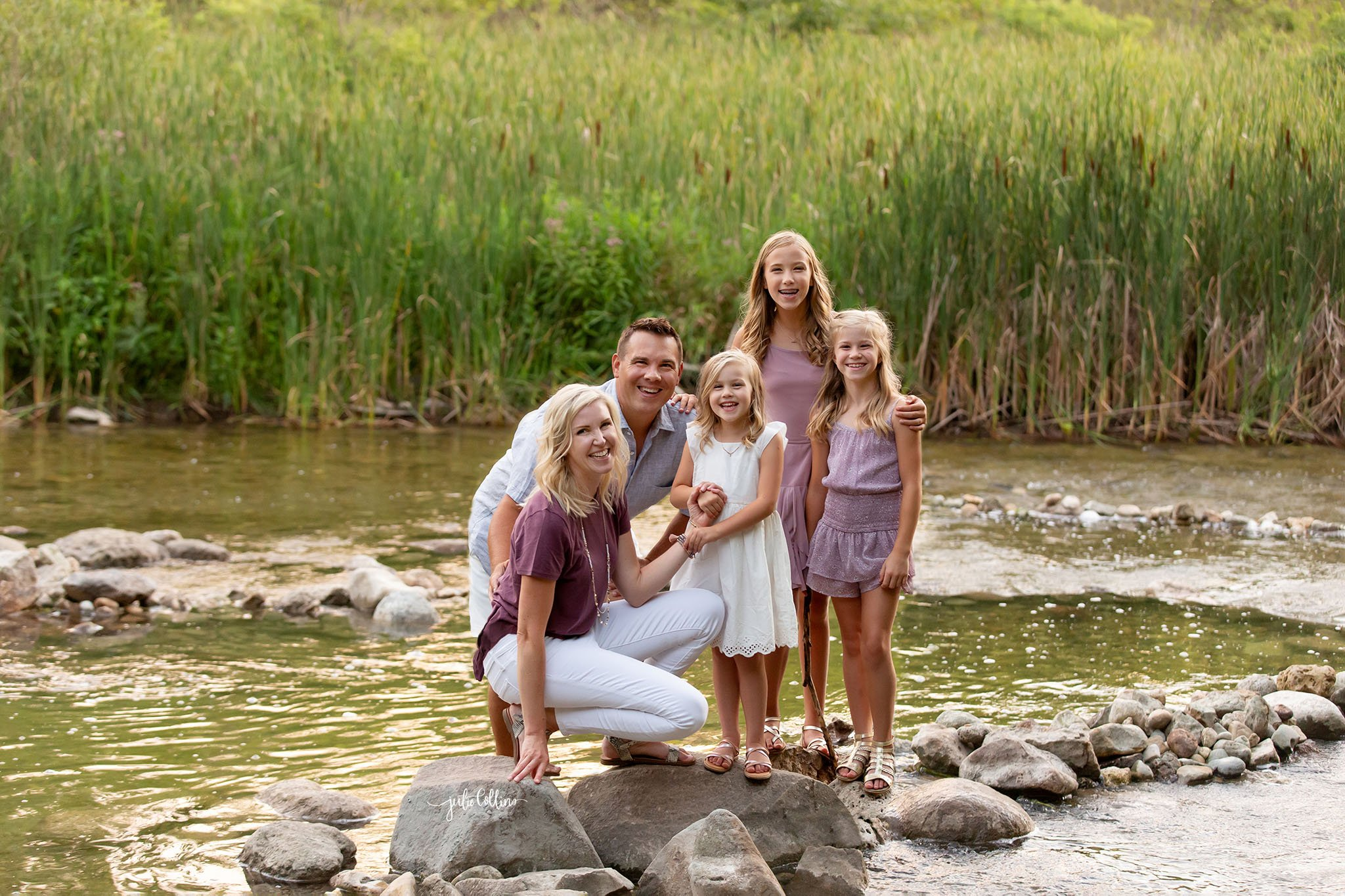 Family of five with three sisters in middle of river for family pictures at Cushing Park, Delafield, Wisconsin