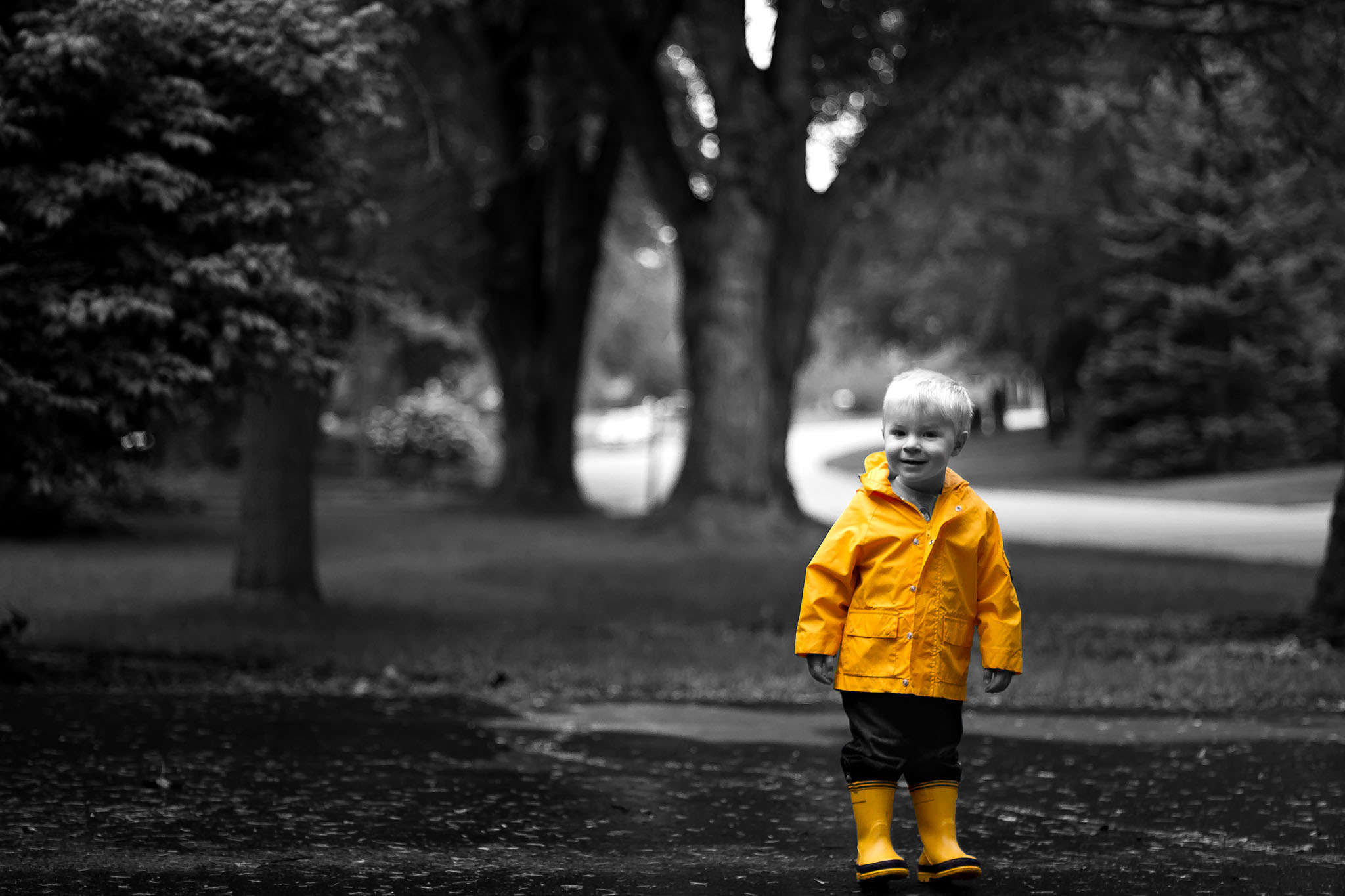 Two year old boy in yellow raincoat demonstrating selective color photography