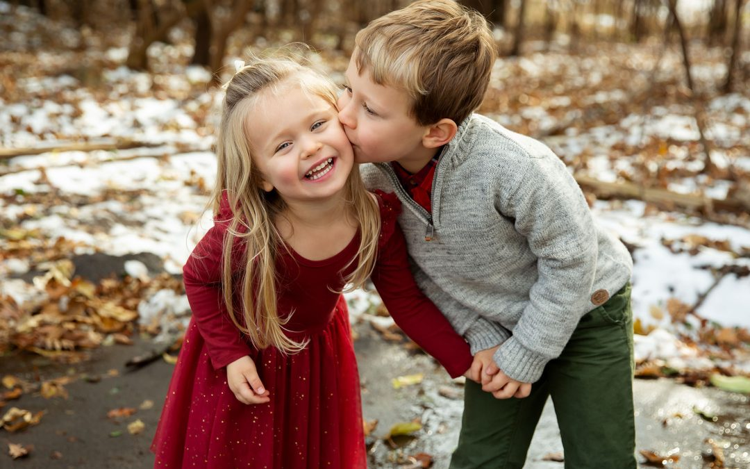 Two kids posing for family photos in Wisconsin winter