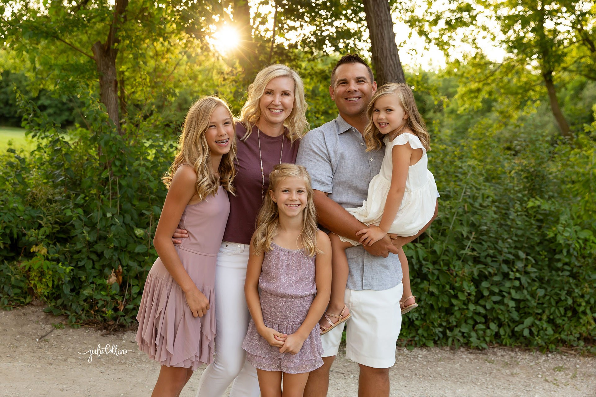 Family of five smiling for camera during family photo session at Cushing Park in Delafield, Wisconsin