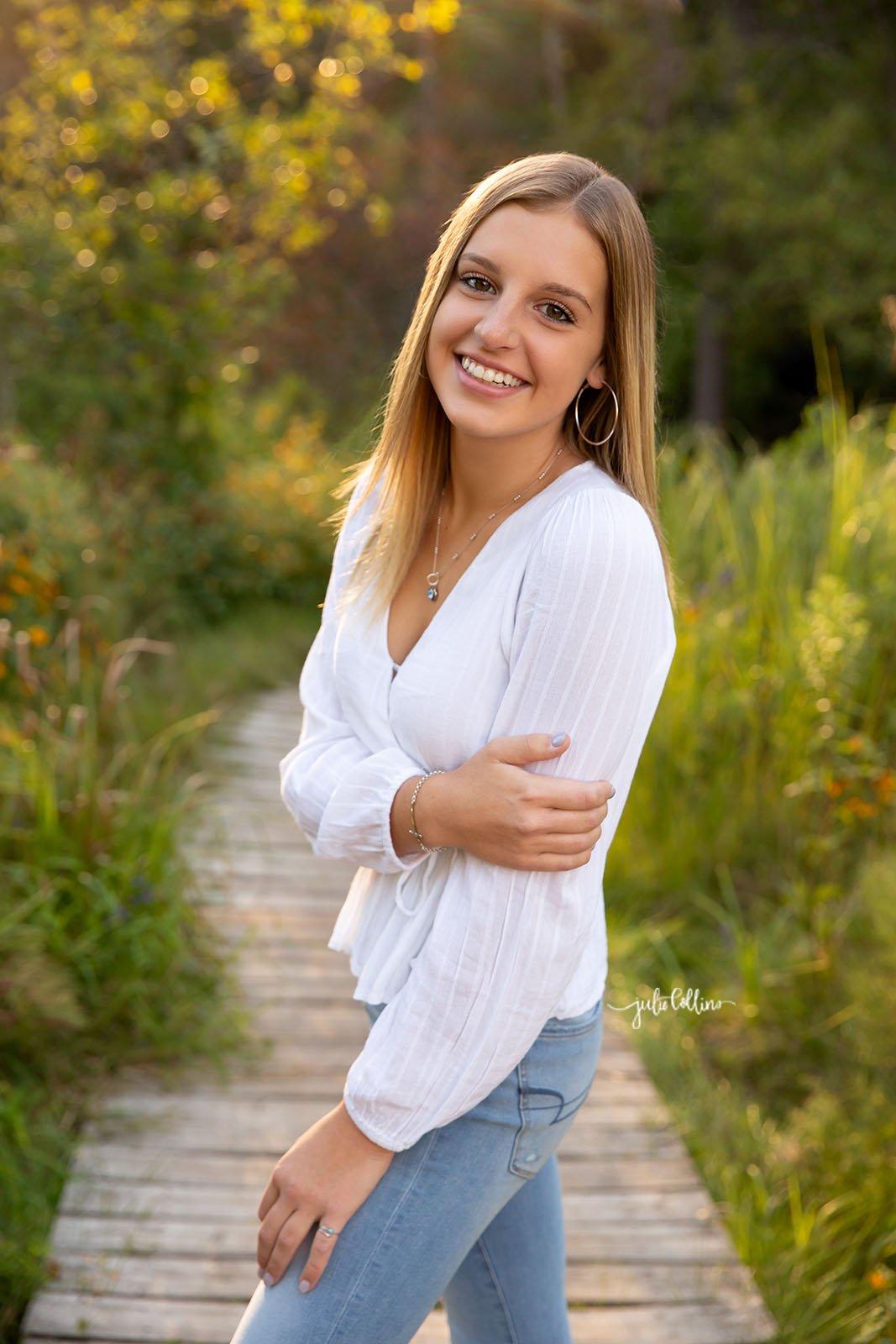 High school senior girl standing in park smiling for camera