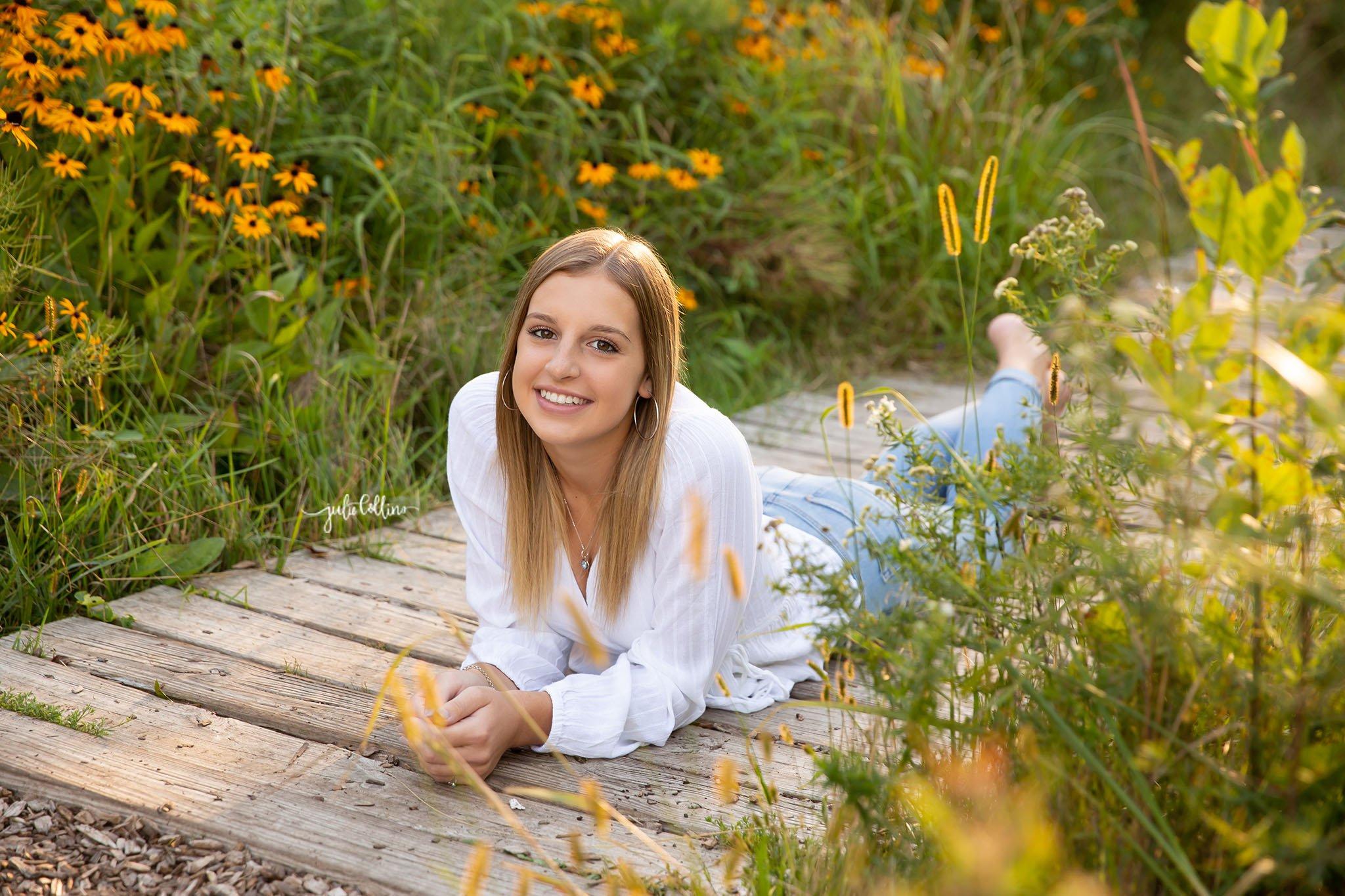 Senior girl in high school lying in flowers
