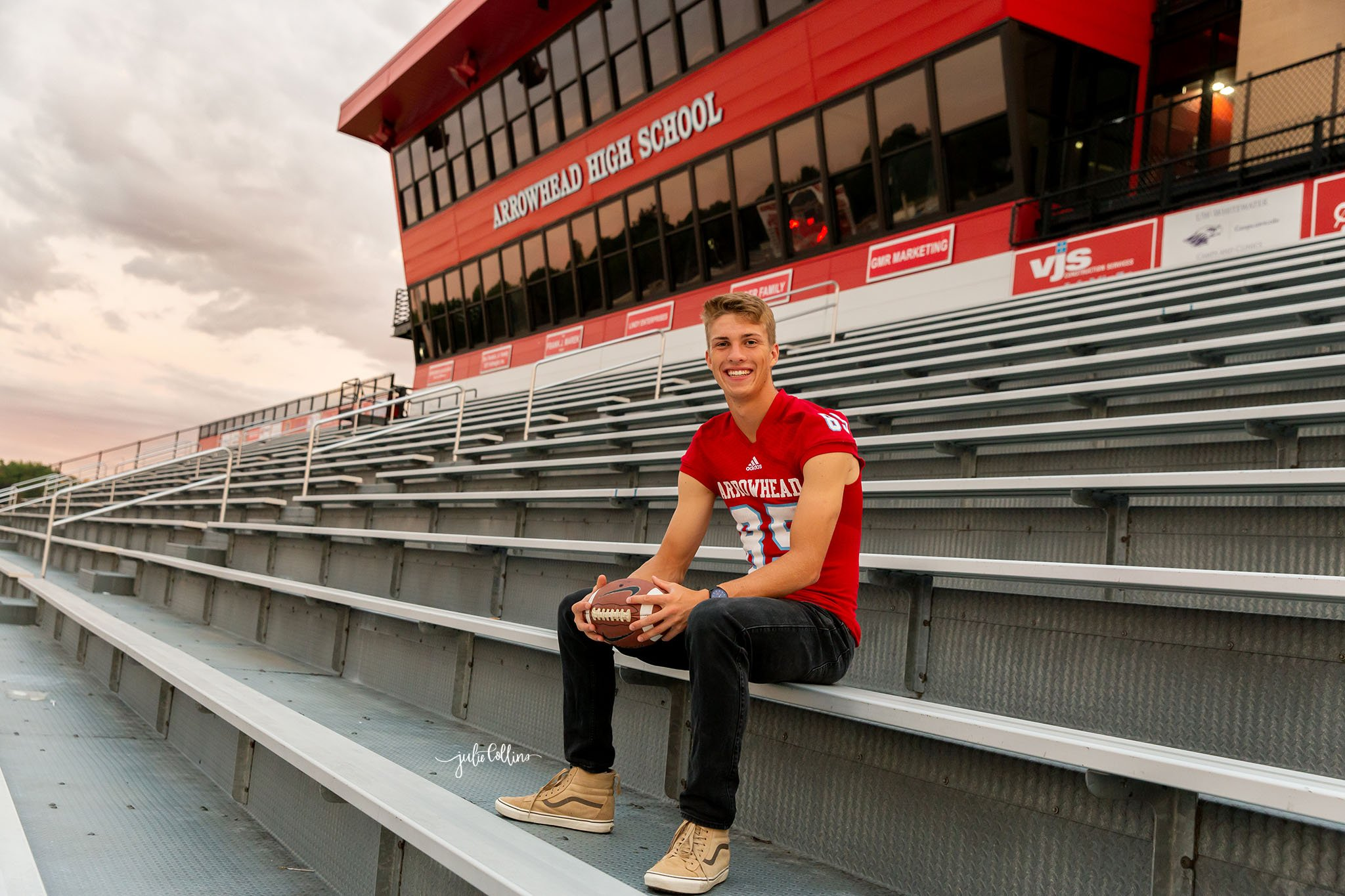 High school senior boy posing for pictures in front of Hartland Arrowhead football stadium in Wisconsin
